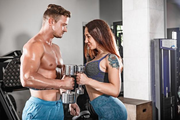 Sport in forma coppia in palestra. lavorare in coppia con manubri Foto Gratuite