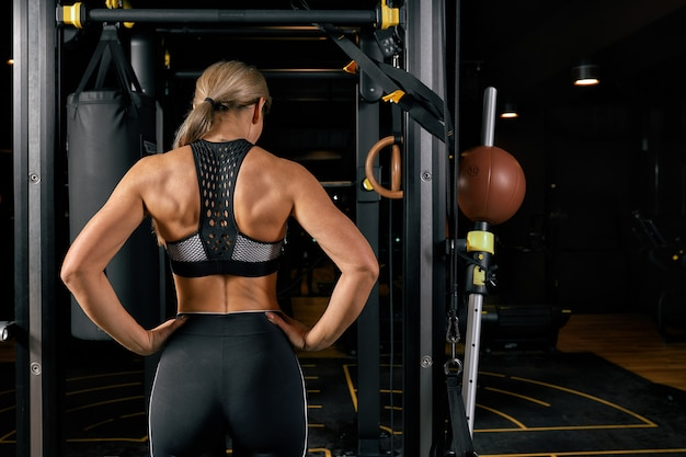 Sport, fitness, lifestyle and people concept. woman exercising and doing pull-ups in gym from back Premium Photo