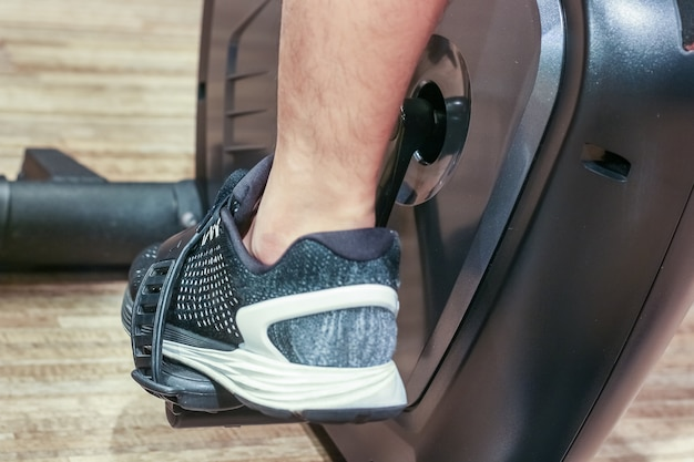 Sport, fitness, lifestyle, technology and people concept - close up of men legs on bicycle in gym Premium Photo