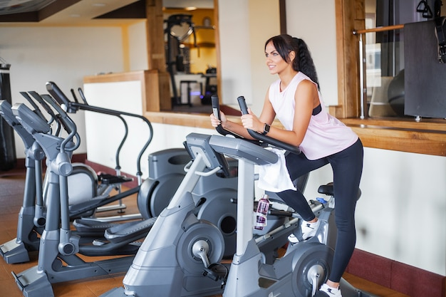 Of sport and healthy lifestyle. exercising legs doing cardio workout on cycling bike Premium Photo
