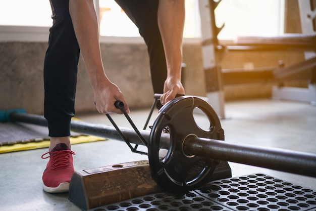 Sport man exercise workout with dumbbell in the gym Premium Photo