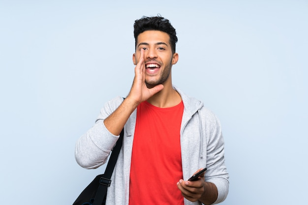 Sport man over isolated blue wall shouting with mouth wide open Premium Photo
