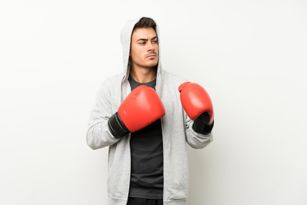 Sport man over isolated white wall with boxing gloves Premium Photo