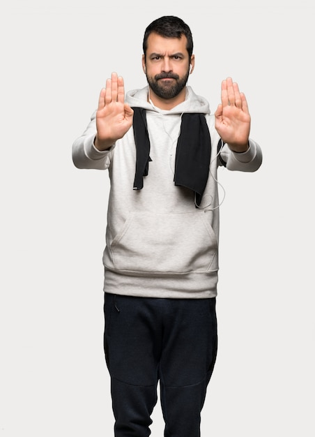 Sport man making stop gesture for disappointed with an opinion over isolated grey background Premium Photo