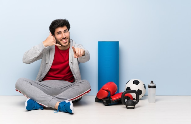 Sport man sitting on the floor making phone gesture and pointing front Premium Photo
