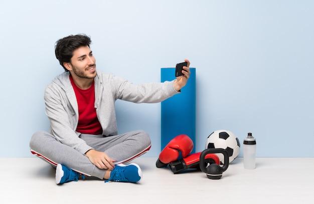 Sport man sitting on the floor making a selfie Premium Photo