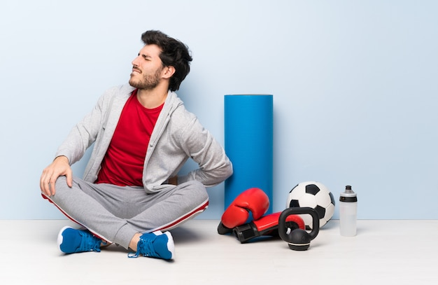 Sport man sitting on the floor suffering from backache for having made an effort Premium Photo