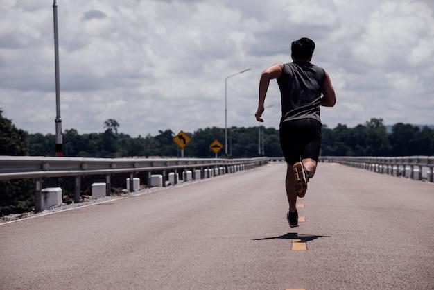 路上でランナーを持つスポーツ男が運動を実行していること 無料写真