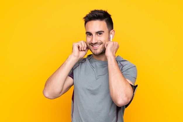 Sport man over yellow wall listening music Premium Photo