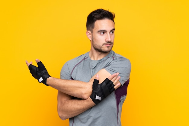 Sport man over yellow wall stretching arm Premium Photo