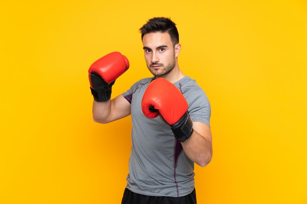 Sport man over yellow wall with boxing gloves Premium Photo
