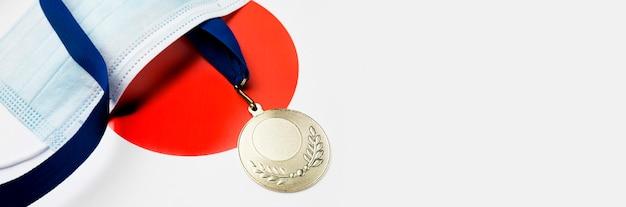 Спортивная медаль рядом с медицинской маской с копией пространства Бесплатные Фотографии