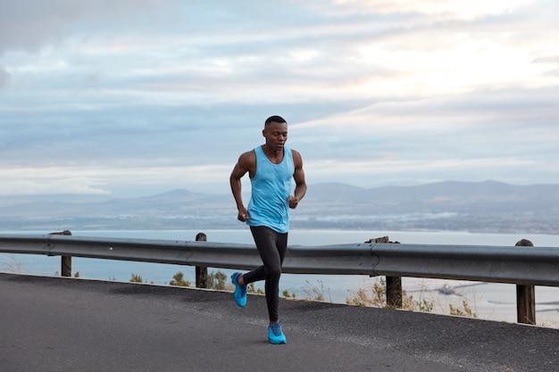 Concetto di sport, motivazione e ricreazione. pareggiatore nero sportivo maschile attivo corre contro il cielo senza nuvole in autostrada, indossa gilet casual e scarpe sportive blu, ha i bicipiti sulle braccia, fa esercizi all'aperto. Foto Gratuite