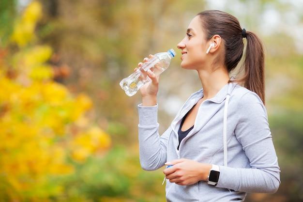 Sport outdoor. woman drinking water after running Premium Photo