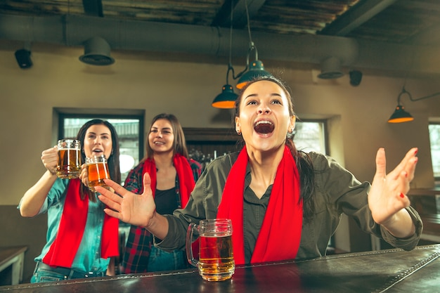 Sport, people, leisure, friendship, entertainment concept - happy female football fans or good young friends drinking beer, celebrating victory at bar or pub. human positive emotions concept Free Photo