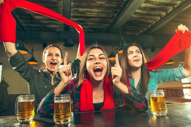 スポーツ、人々、レジャー、友情、エンターテインメントのコンセプト-幸せな女性のサッカーファンやビールを飲み、バーやパブでの勝利を祝う良い若い友人。人間のポジティブな感情の概念 無料写真