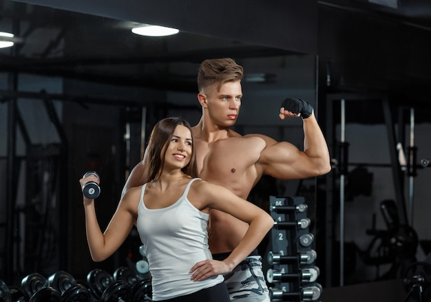 Sport, training, fitness, lifestyle and people concept - young woman with personal trainer flexing back and abdominal muscles on bench in gym Premium Photo