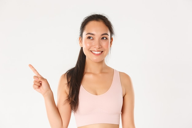 Sport, wellbeing and active lifestyle concept. close-up of smiling attractive asian fitness girl, female athlete picking new gear in store, pointing and looking upper left corner pleased. Free Photo