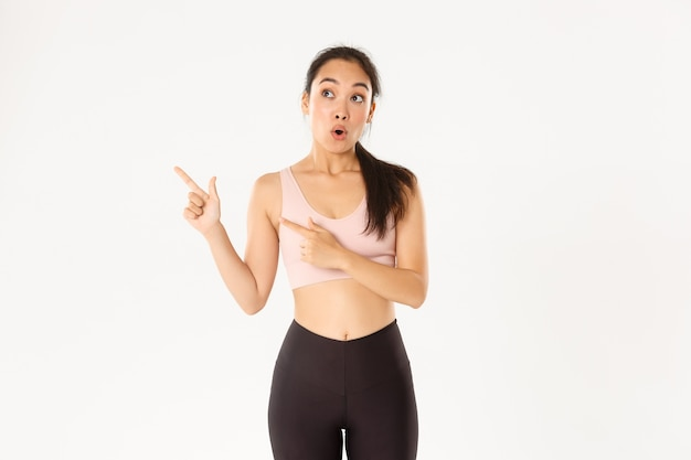 Sport, wellbeing and active lifestyle concept. impressed and excited sportswoman, asian athlete in activwear open mouth wondered and pointing fingers upper left corner at your logo banner. Free Photo