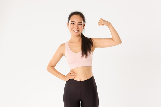 Sport, wellbeing and active lifestyle concept. portrait of smiling slim and strong asian fitness girl, personal workout trainer showing muscles, flexing biceps and look proud, white background. Free Photo
