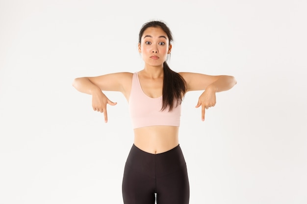 Sport, wellbeing and active lifestyle concept. startled and impressed asian fitness girl, gym member or sportswoman in activewear pointing fingers down, looking speechless, white background. Free Photo