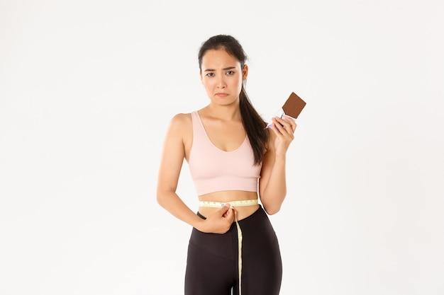Концепция спорта, благополучия и активного образа жизни. разочарованная мрачная азиатская девушка измеряет талию рулеткой и дуется, потому что не может есть плитку шоколада при похудении на диете. Бесплатные Фотографии