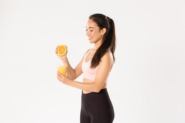 Концепция спорта, благополучия и активного образа жизни. портрет улыбающейся здоровой и стройной азиатской девушки советует есть здоровую пищу на завтрак, набираться энергии для хорошей тренировки, выжимать апельсиновый сок в стакане Premium Фотографии