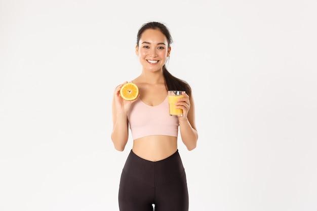 スポーツ、健康、アクティブなライフスタイルのコンセプト。朝食に健康的な食べ物を食べて健康的でスリムなアジアの女の子の笑顔の肖像画、トレーニングのエネルギーを得て、フレッシュジュースとオレンジを保持 無料写真