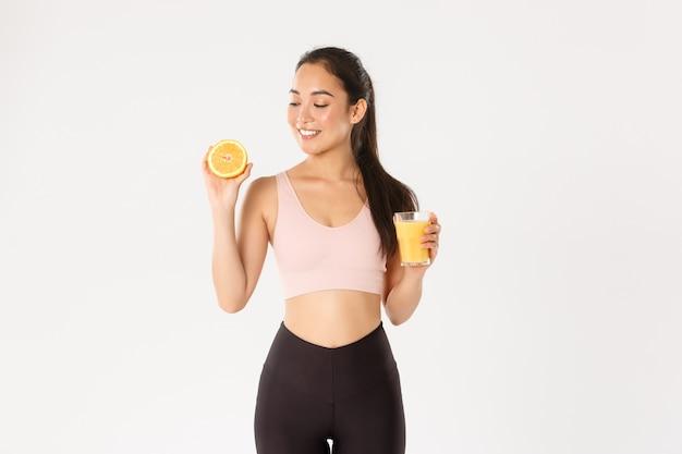 スポーツ、幸福、アクティブなライフスタイルのコンセプト。朝食に健康的な食べ物を食べ、トレーニングのためのエネルギーを獲得し、フレッシュジュースとオレンジを保持する健康的でスリムなアジアの女の子のアドバイスを笑顔の肖像画 Premium写真