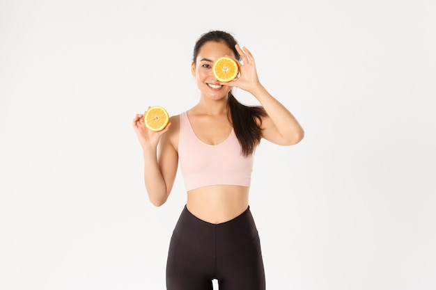 スポーツ、健康、アクティブなライフスタイルのコンセプト。健康的でスリムなアジアの女の子の笑顔の肖像画朝食に健康食品を食べる、ワークアウトのエネルギーを得る、オレンジ色の2つの半分を保持する。 Premium写真