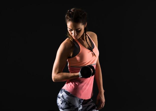 Sport woman on dark background making weightlifting Premium Photo