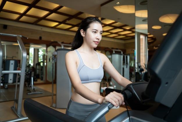 Sport woman walk on cardio machine at the gym Premium Photo