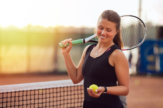 Sportive beautiful girl looking at tennis ball, standing on the court with racket. Free Photo