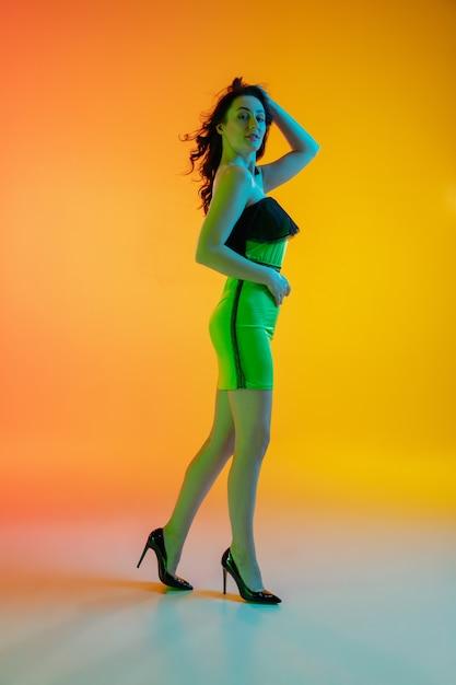Спортивный. красивая соблазнительная девушка в модном купальнике на градиентном оранжевом фоне в неоновом свете. Бесплатные Фотографии