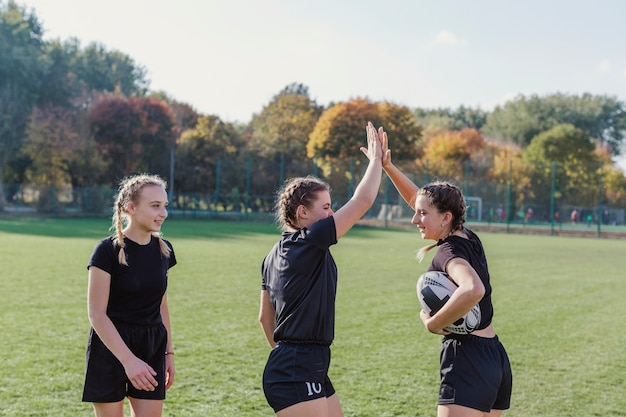 Sportive girls holding soccer ball and high five Free Photo
