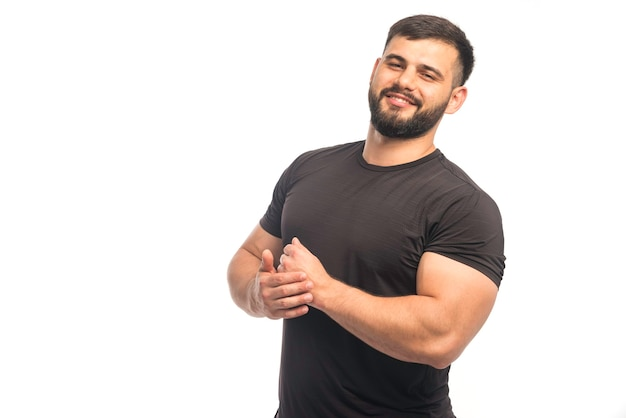 Sportive man in black shirt demonstrating his arm muscles and looks positive Free Photo