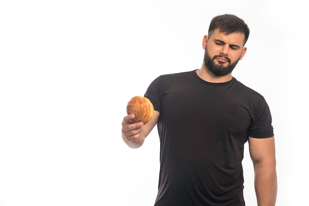 Sportive man in black shirt holding a doughnut and refusing Free Photo