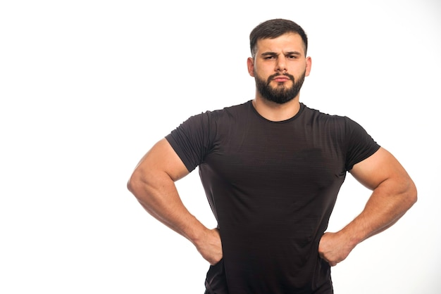 Sportive man in black shirt putting his hand to his waist Free Photo
