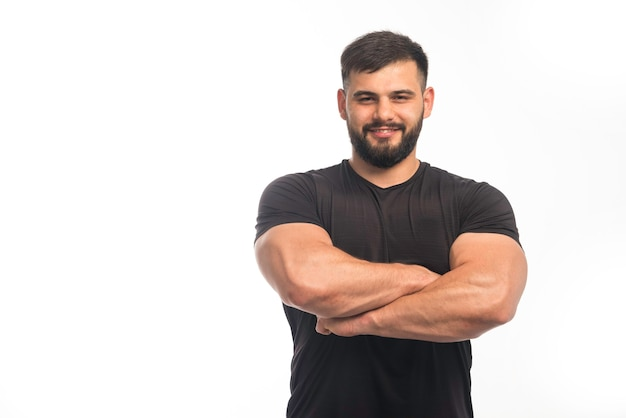 Спортивный мужчина в черной рубашке закрывает мышцы рук Бесплатные Фотографии