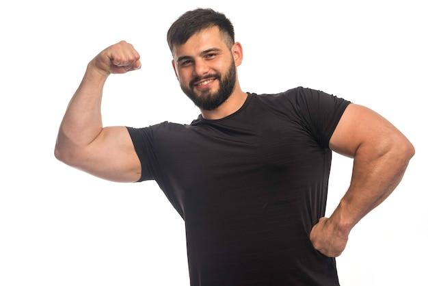 Спортивный мужчина в черной рубашке чувствует себя сильным Бесплатные Фотографии
