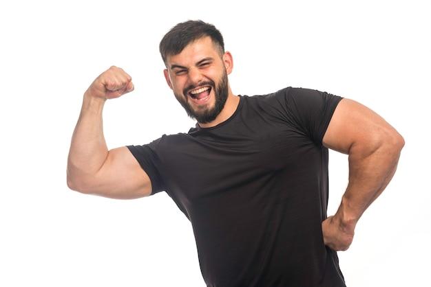 強い感じの黒いシャツを着たスポーティーな男。 無料写真
