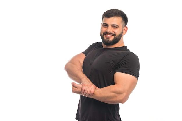 Спортивный мужчина в черной рубашке, прикладывая руку к мышцам руки Бесплатные Фотографии