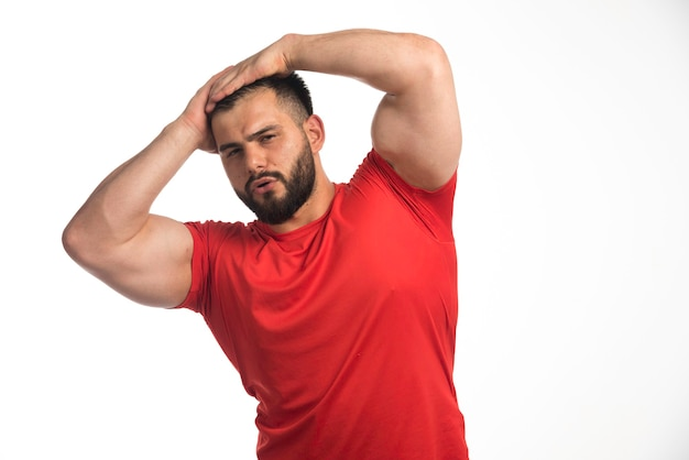 Sportive man in red shirt demonstrating his muscles and put hands to his head. Free Photo