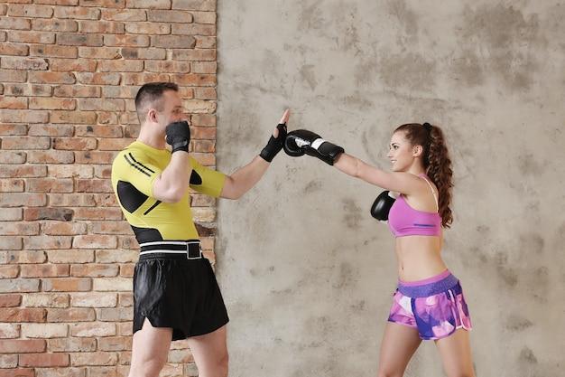 彼のガールフレンドにボクシングのテクニックを示すスポーティーな男 無料写真