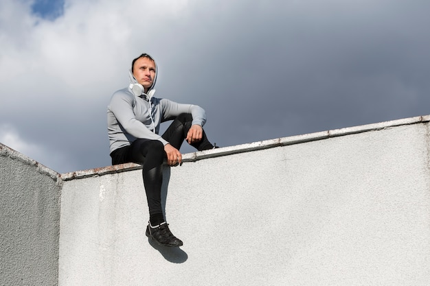Sportive man sitting on a wall and looking away Free Photo
