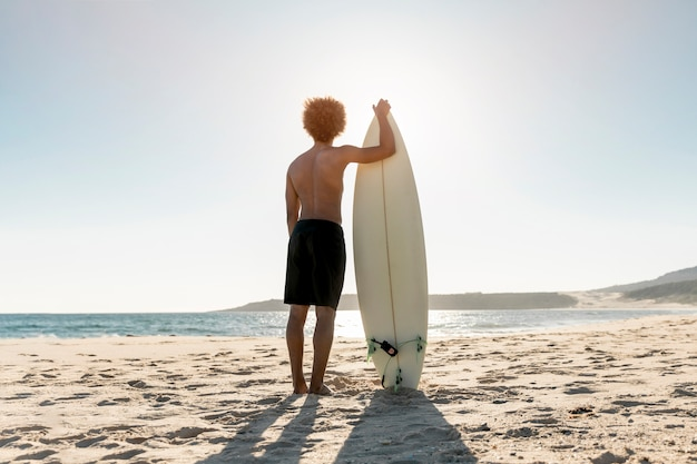 Sportive man standing on seashore with surfboard Free Photo
