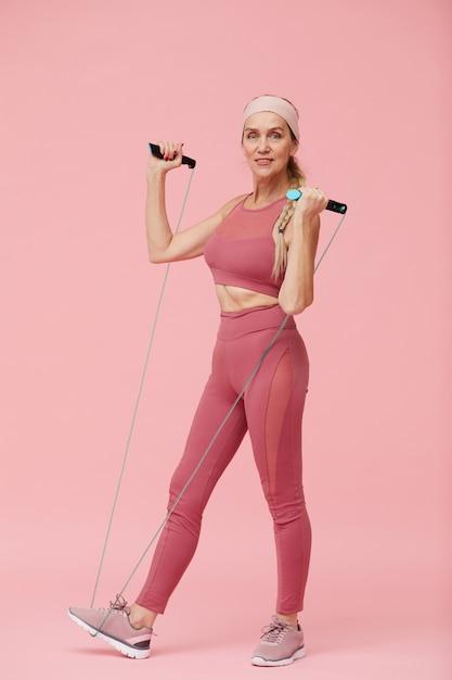 Спортивная зрелая женщина позирует со скакалкой Premium Фотографии