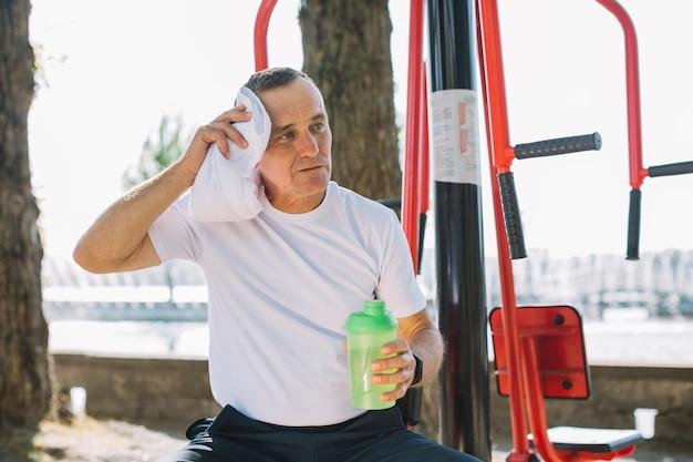 Sportive senior wiping perspiration Free Photo