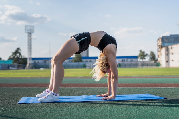 Sportive woman in bridge pose on mat Free Photo
