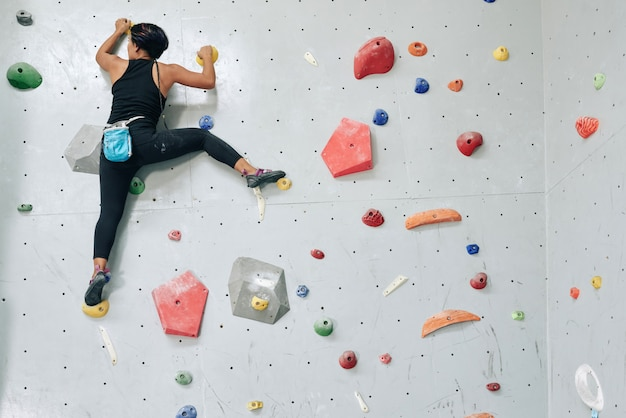 Sportive woman clambering wall in gym Free Photo